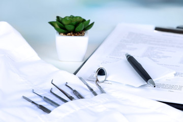 Dentist tools in pocket of medical robe on table close up