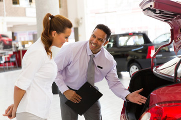 car salesman showing new vehicle to customer