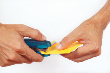 Hands bonded colored paper stapler on a white background
