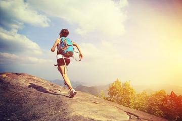 woman hiker running at on mountain peak rock