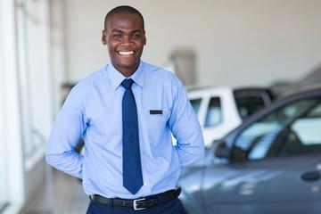 afro american salesman working at vehicle showroom