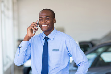 african american car salesman talking on cell phone
