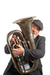 A man wearing a hat and blazer playing a vintage silver Tuba isolated on a white background