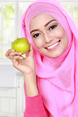 young muslim woman holding an apple