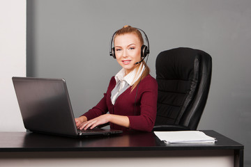 businesswoman talking by the phone while working on her computer