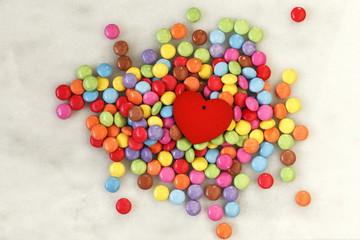 Schokolinsen, Smarties auf Marmor, rotes Herz