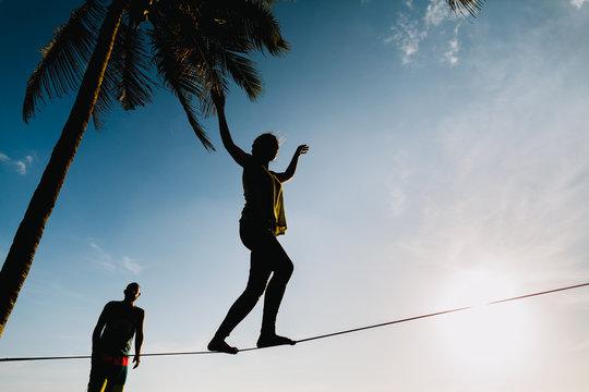 teenagers balancing on slackline with sky view