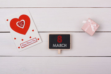 Blackboard with 8 march tag, a gift and a card with red hearts o