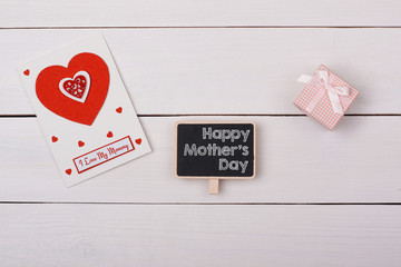 Blackboard with happy mathers day tag, a gift and a card with re