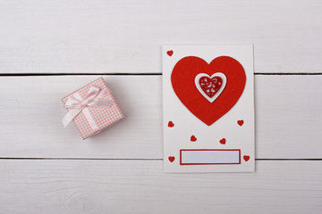 A gift and a card with red hearts on the table.