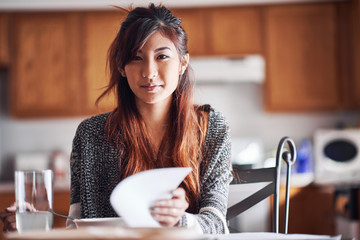 asian teen girl with homework in kitchen