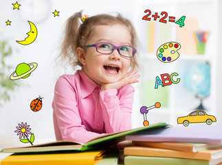 Funny smart kid in glasses reading book in kindergarten
