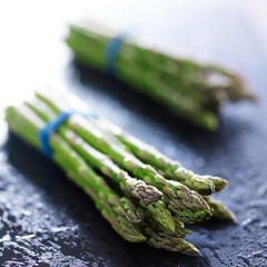 side view of two bunches of fresh asparagus