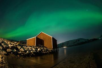 Aurora Borealis reflected on a lake with house