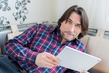 Man sitting in sofa using electronic tablet