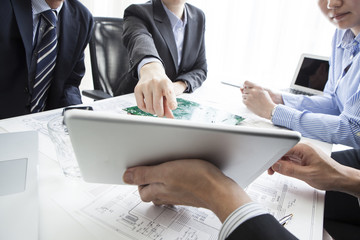 Woman the tablet is pointing in a meeting