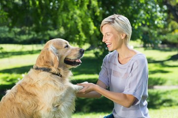 Pretty blonde playing with her dog in the park