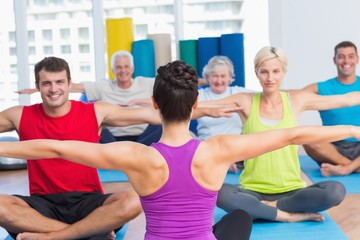 People practicing yoga in health club