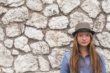 Girl in a hat and denim jacket against a white stone walls.