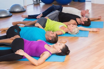 People stretching legs in fitness studio