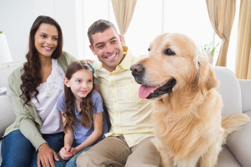 Family sitting with Golden Retriever on sofa