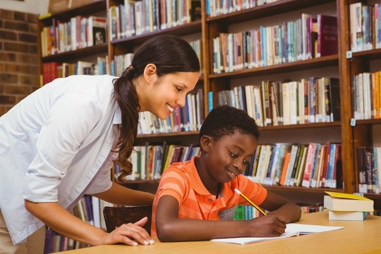 Teacher assisting mixed race boy with homework in library