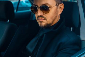 Elegant male in black suit driving car