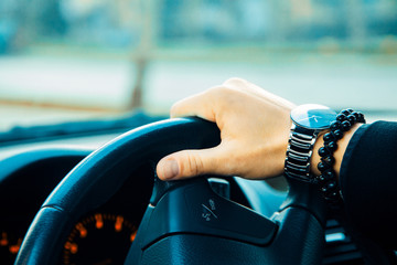 Male hand with bracelet and watch driving a car