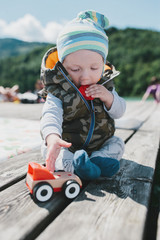 Cute young baby boy playing with a truck