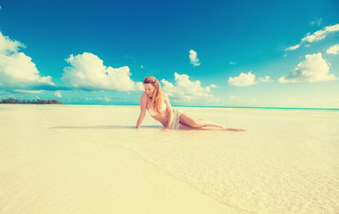woman laying on beach yellow sand with tropical blue sky ocean b