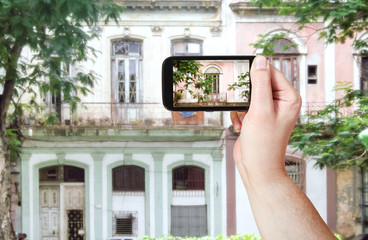 tourist taking photo of old building in Havana