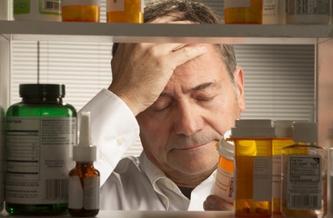 white male looking at assortment of prescription drugs