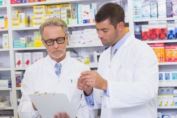 Senior pharmacist writing on clipboard