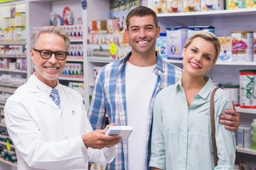 Pharmacist and costumers smiling looking at camera