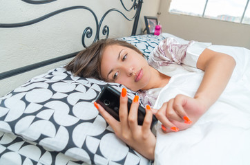 young teen girl lying in bed with her cell phone
