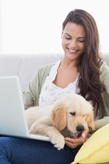 Woman with dog using laptop on sofa