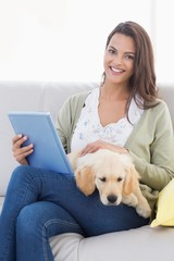Woman with dog using tablet computer on sofa