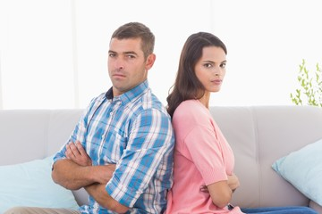 Angry couple sitting arms crossed on sofa