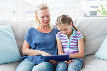 Mother with daughter using digital tablet on sofa