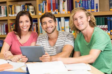 College students using digital tablet in library