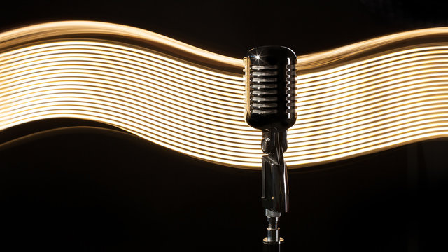 Vintage retro microphone on the black background with light wave