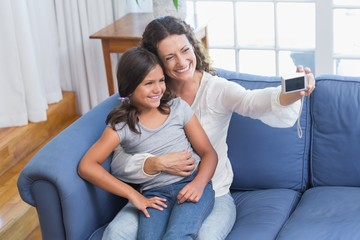 Happy mother and daughter sitting on the couch and taking selfie