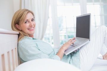 Happy woman using laptop in her bed