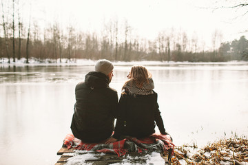 Young couple sitting on pier at frozen lake looking at each othe
