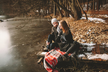 Couple sitting on pier at frozen lake looking at each other