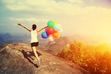 young asian woman mountain peak  running with colored balloons