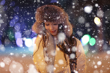 winter night portrait of a beautiful girl, snowflakes, fur hat