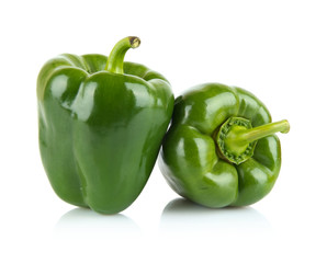 Close-up shot of two green bell peppers isolated on white