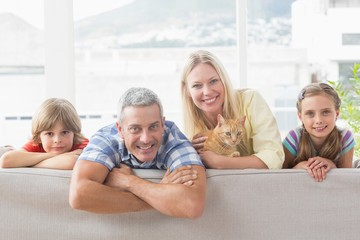 Happy family with cat on sofa at home