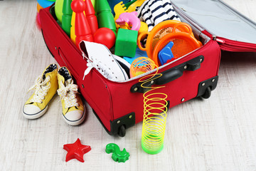 Suitcase packed with clothes and child toys
